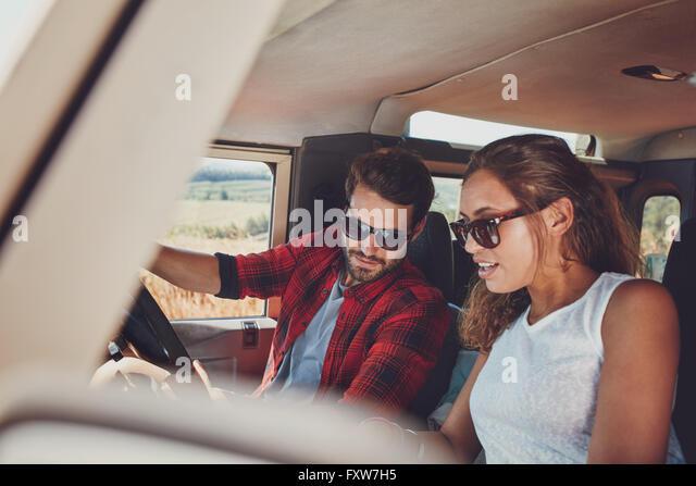 Junges Paar in ihrem Auto sitzen und mit Blick auf etwas Interessantes. Junger Mann und Frau zusammen zu sitzen Stockbild