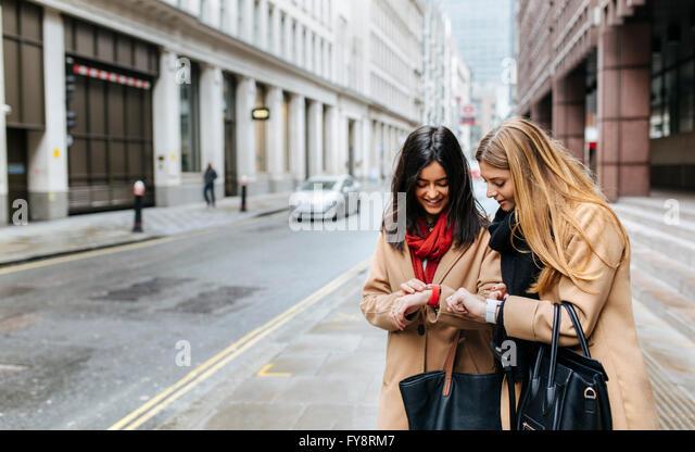 UK, London, zwei Freunde, die Erkundung der Stadt überprüft smart-Uhren Stockbild