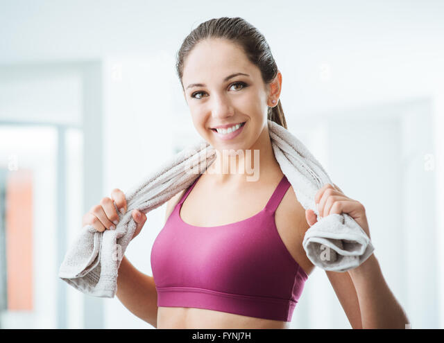 Schöne sportliche Frau mit Handtuch entspannen, im Fitnessstudio trainieren, gesunde Lebensweise und Fitness Stockbild