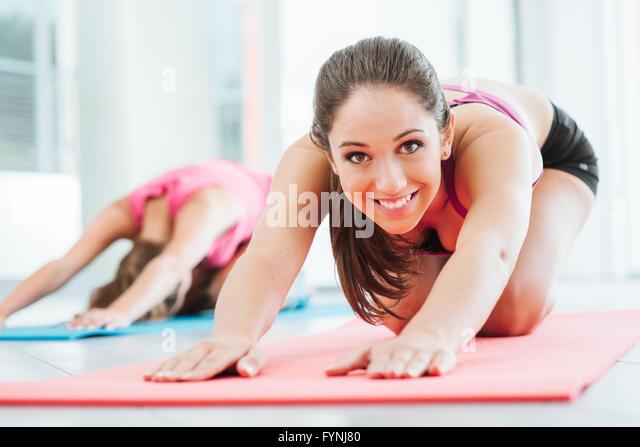 Mädchen in der Turnhalle stretching-Übungen auf der Matte zu tun, eine in die Kamera lächelt Stockbild