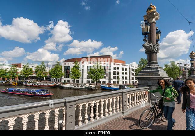 Opernhaus, Kanalboote, Mädchen mit dem Fahrrad, Amsterdam, Niederlande Stockbild