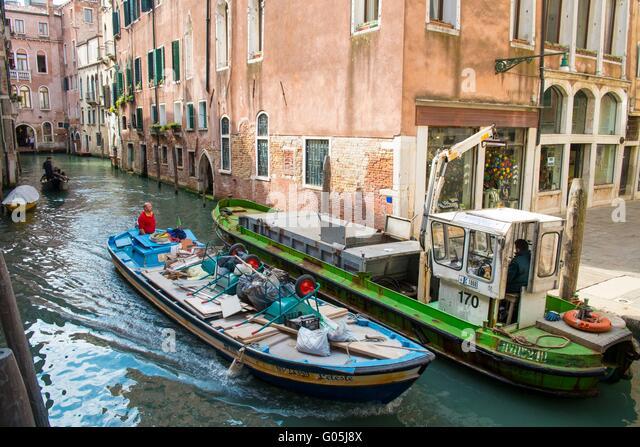 Ein Erbauer Kanalboot übergibt ein Müll Lastkahn auf eine venezianische Wasserstraße, Venedig, Italien, Stockbild