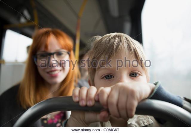 Porträt neugieriger Junge Reiten Bus mit Mutter Stockbild
