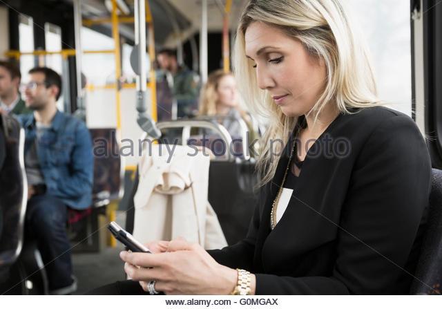 Geschäftsfrau SMS mit Handy auf bus Stockbild