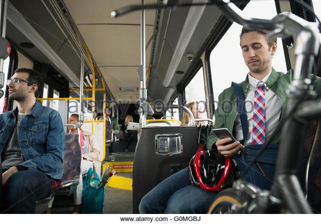 Geschäftsmann mit dem Fahrrad Texting auf bus Stockbild