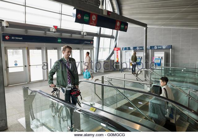 Geschäftsmann mit Fahrrad auf Rolltreppe im Bahnhof Stockbild