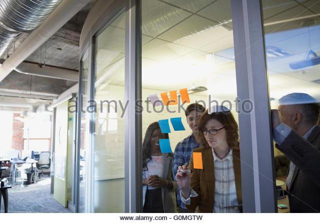 Brainstorming mit Klebstoff Notizen Konferenzraum Geschäftsleute Stockbild