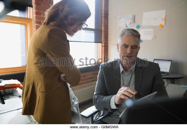 Unternehmer und Unternehmerin mit digital-Tablette Schreibtisch - Stock-Bilder