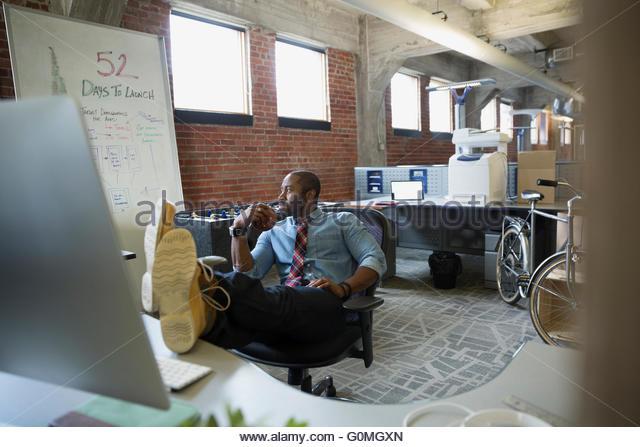 Unternehmer mit den Füßen oben auf neues Büro Schreibtisch Stockbild
