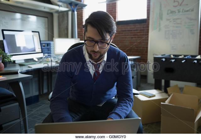 Unternehmer mit Laptop im neuen Büro Stockbild