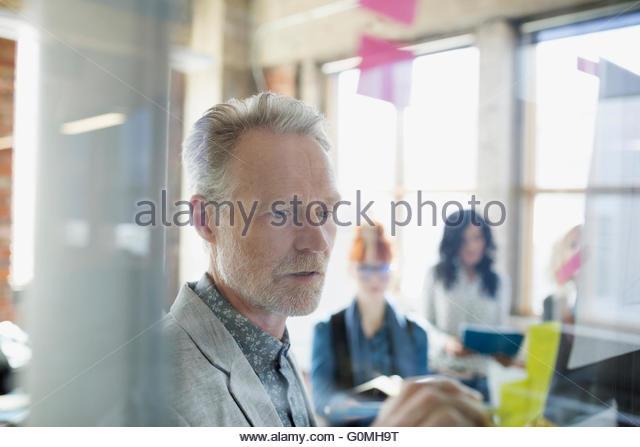 Geschäftsmann schreiben auf Klebstoff Hinweis auf Büro-Glas Stockbild