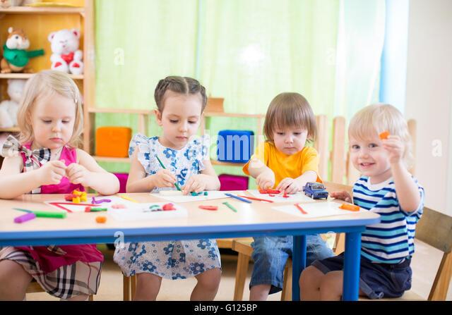 Kids-Gruppe mit Interesse Kunstgewerbe in Day Care Center Spielzimmer lernen Stockbild