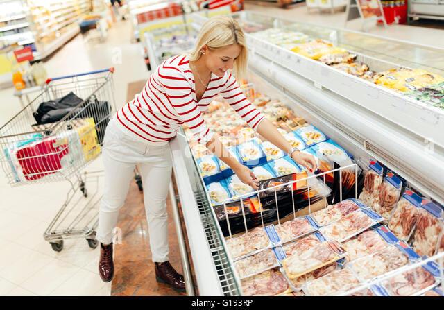 Schöne Frau einkaufen und Essen im Supermarkt zu wählen Stockbild