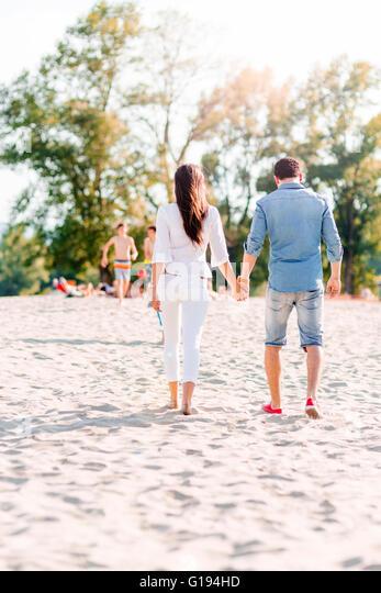 Paar Hand in Hand und Fuß an einem Sandstrand - Stock-Bilder