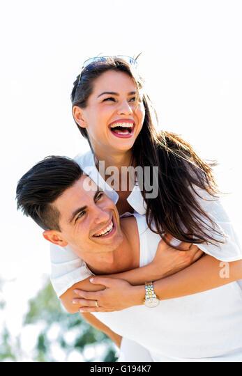 Fröhliche gut aussehender Mann mit seiner Freundin auf dem Rücken am Strand Stockbild