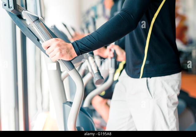 Junge gesunde Gruppe von Menschen, die Arbeiten auf eine elliptische Trainer in einem Fitnesscenter Stockbild