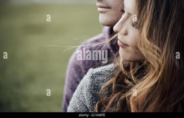 Junges Liebespaar im Freien sitzen auf dem Rasen, umarmt und wegsehen, Zukunft und Beziehungen-Konzept Stockbild