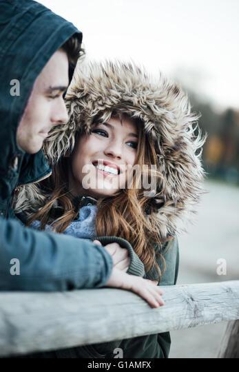 Lächelnd Liebespaar mit Hauben Datierung während einer kalten Winter Tag, Liebe und Beziehungen-Konzepts Stockbild