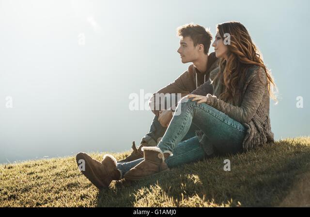 Lächelnd junges Paar sitzt auf dem Rasen an einem sonnigen Tag, wegsehen und über ihre Zukunft träumen Stockbild