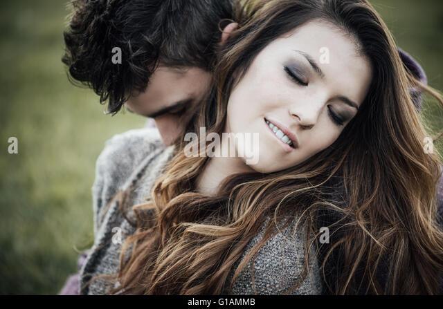 Romantisch zu zweit im Freien, sie sitzen auf dem Rasen und umarmt, beißt sie ihre Lippen Stockbild