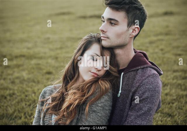 Junge Teenager im Freien, auf dem Rasen sitzen und kuscheln, umarmt er seine Freundin, Beziehungen und Gefühle Stockbild