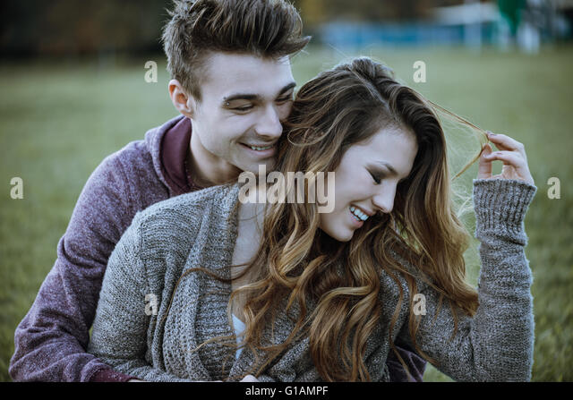 Verspielte junge Paar sitzen auf dem Rasen und umarmt, sie lachen genießen und Stockbild