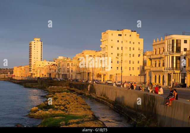 Kuba, Provinz Ciudad De La Habana, Havana, Kubaner auf dem Malecon und der Leuchtturm von Castillo de Los Tres reyes Stockbild
