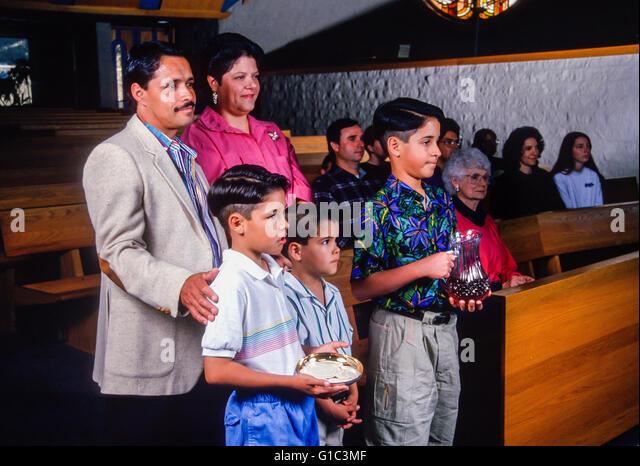 Hispanische Familie bringen Geschenke auf dem Altar in der katholischen Kirche. Herr © Myrleen Pearson Stockbild