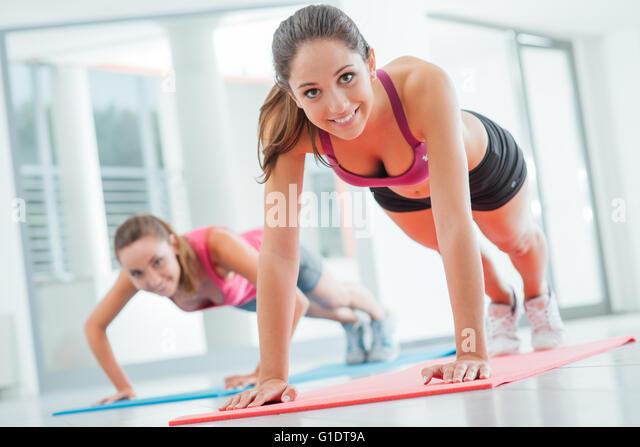 Junge Frauen in der Turnhalle tun Push Ups auf einer Matte, Fitness und gesunden Lifestyle-Konzept Stockbild