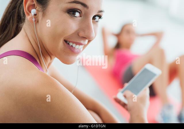 Junge lächelnde Frau in der Turnhalle eine Pause und anhören von Musik über ein smart Phone und Kopfhörer, Stockbild