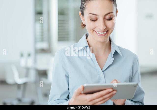 Junge Geschäftsfrau mit einem digital Touch-Screen-Tablette und apps mit Lächeln, steht sie im Büro Stockbild