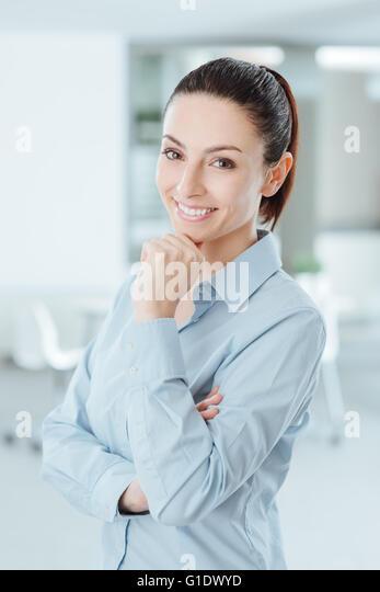 Selbstbewusste Frau posiert mit Hand am Kinn und lächelt in die Kamera Stockbild