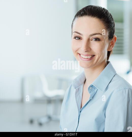 Schöne junge lächelnde Geschäftsfrau lächelnd und Blick in die Kamera, Büroeinrichtung Stockbild