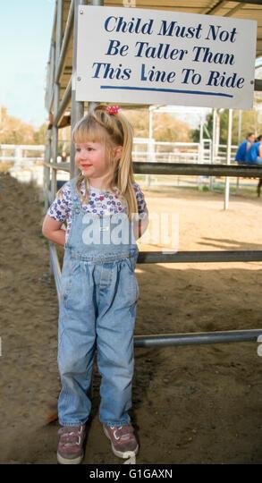 3 Jahre altes Mädchen Überprüfung Zeichen für Höhe Qualifikation Pony reiten © Myrleen Stockbild