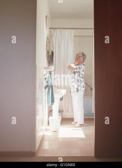 Voller Länge Innenaufnahme älteren Frau, die immer bereit auf die Kommode. Senioren weiblich immer im Stockbild
