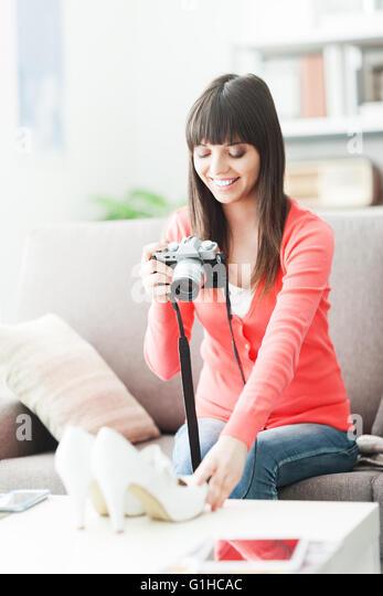 Junge, lächelnde Frau, die ihre Schuhe mit einer Kamera fotografieren, wird sie sie auf einen Online-Shop zu Stockbild
