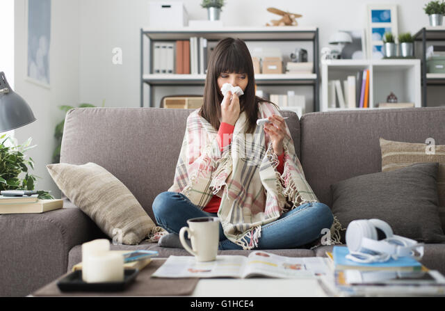 Kranke Frau mit Erkältung und Grippe, ruht sie auf dem Sofa zu Hause und Messung der Körpertemperatur Stockbild