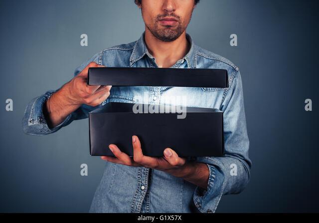 Ein junger Mann ist eine Box mit etwas spannendes drin öffnen. Stockbild