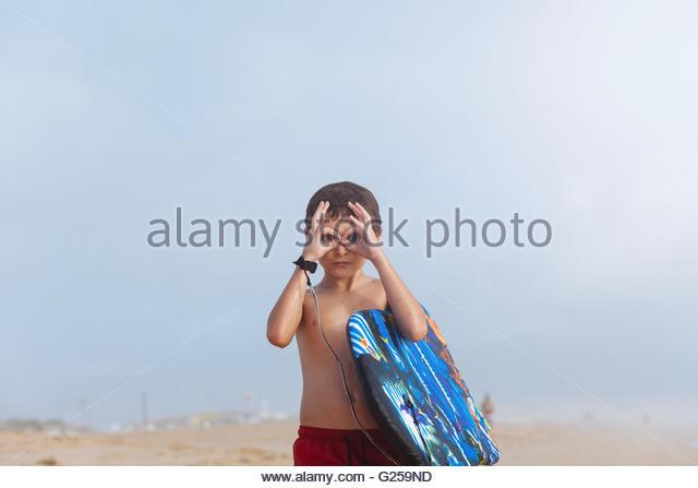 Boy am Strand mit Boogie Board machen vorgeben Fernglas mit Fingern Stockbild