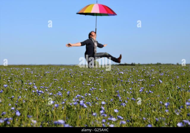 Man balancieren Sonnenschirm am Kinn während Flickschusterei in einem Feld, Niort, Frankreich Stockbild