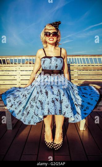 Junge Frau im Retro-Kleid und High Heels auf Bank Boardwalk am Strand sitzen Stockbild