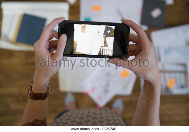 Designer fotografieren Beweise und Unterlagen mit Kamera-Handy Stockbild