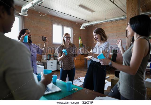 Kreative Geschäftsleute feiert Eröffnung Flasche Champagner im Büro Stockbild