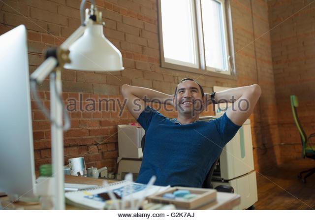 Glücklich kreative Unternehmer sitzen am Schreibtisch mit Händen hinter dem Kopf Stockbild
