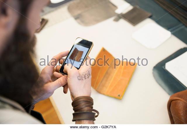 Lederbearbeiter Leder mit Kamera-Handy zu fotografieren Stockbild
