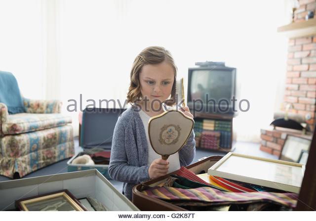 Neugierige Mädchen Blick auf alte Handspiegel Stockbild