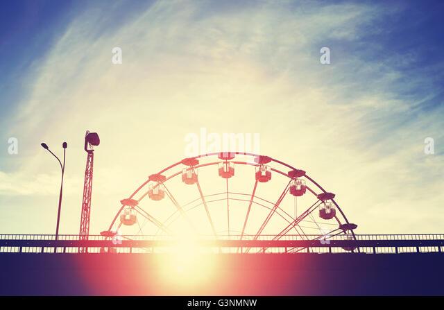 Vintage getönten Sonnenuntergang über ein Vergnügungspark mit Lens-Flare-Effekt. Stockbild