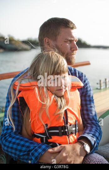 Norwegen, Bergen, Mädchen (4-5) in Rettungsweste auf väterlichen Schoß sitzen Stockbild