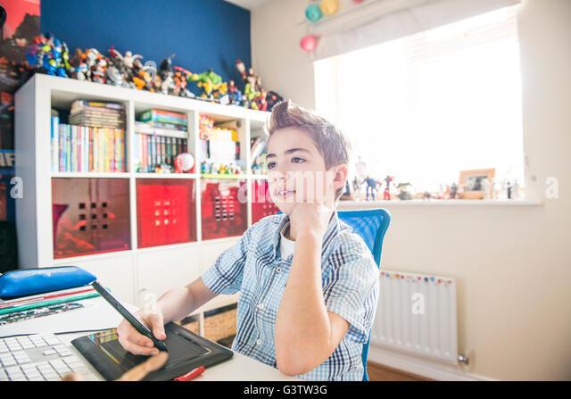 Ein zehn Jahre alter Junge sitzt an einem Computer in seinem Schlafzimmer. Stockbild