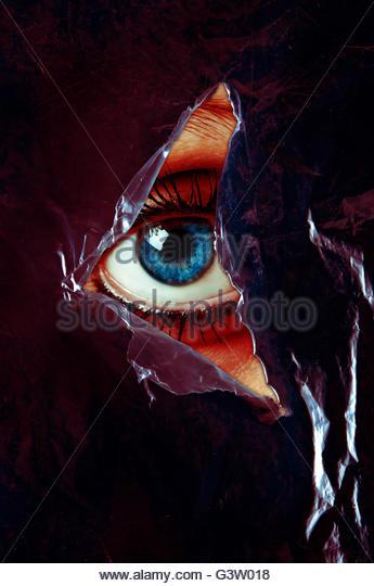blaues Auge einer Frau hinter einer zerrissenen Plastikfolie Stockbild